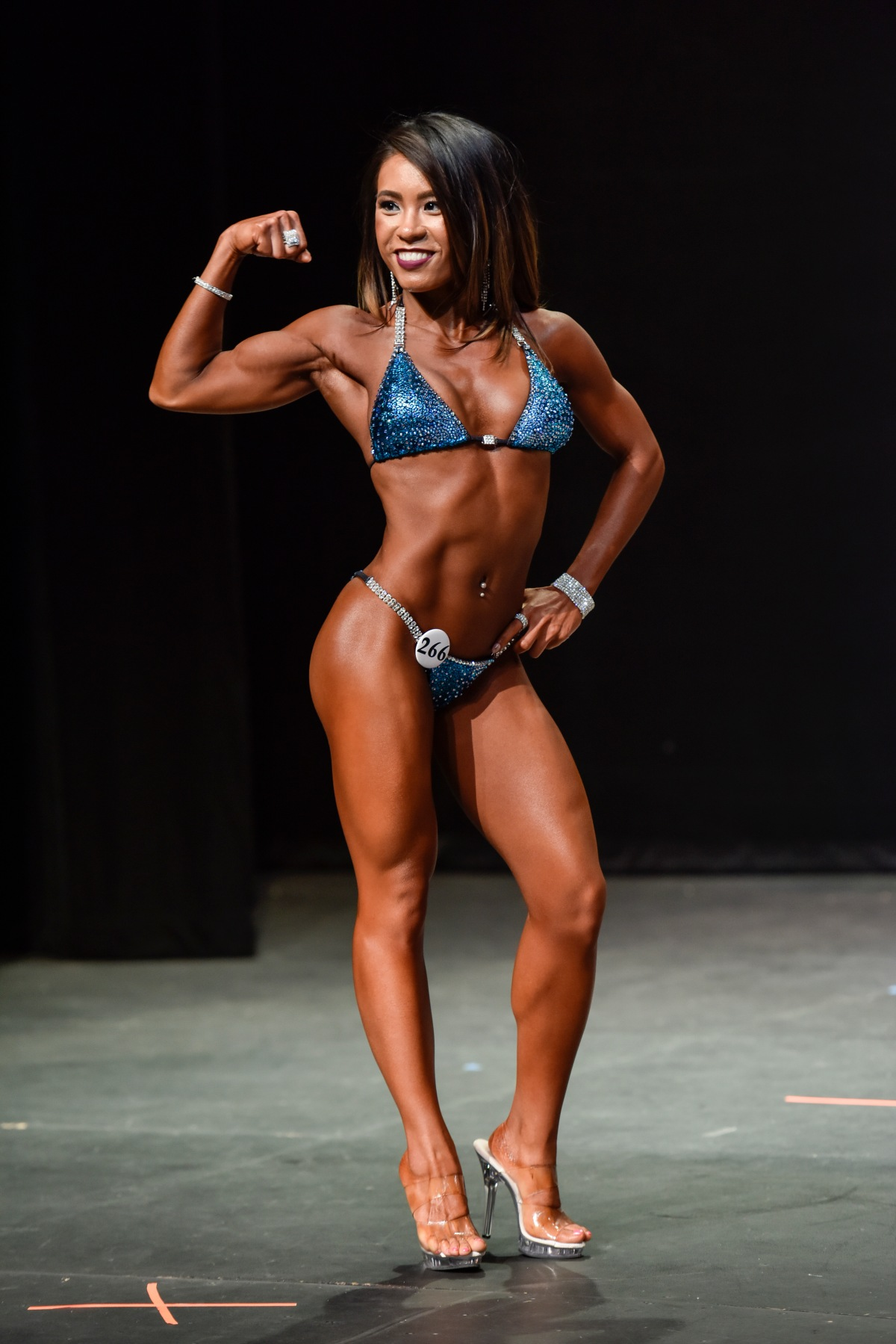 Single bicep pose at bikini fitness competition